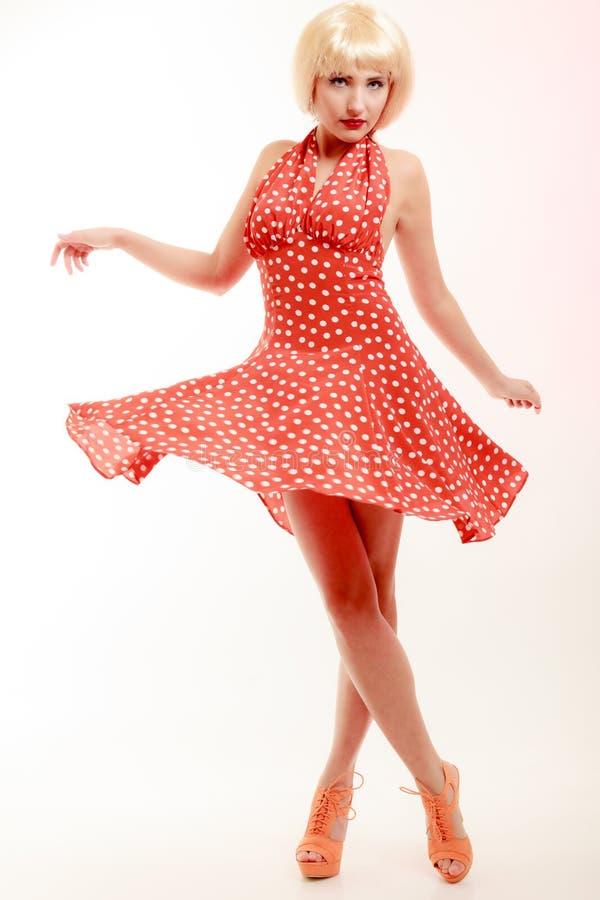 Härlig utvikningsbrudflicka i blond peruk och retro röd klänningdans. Parti. arkivfoton