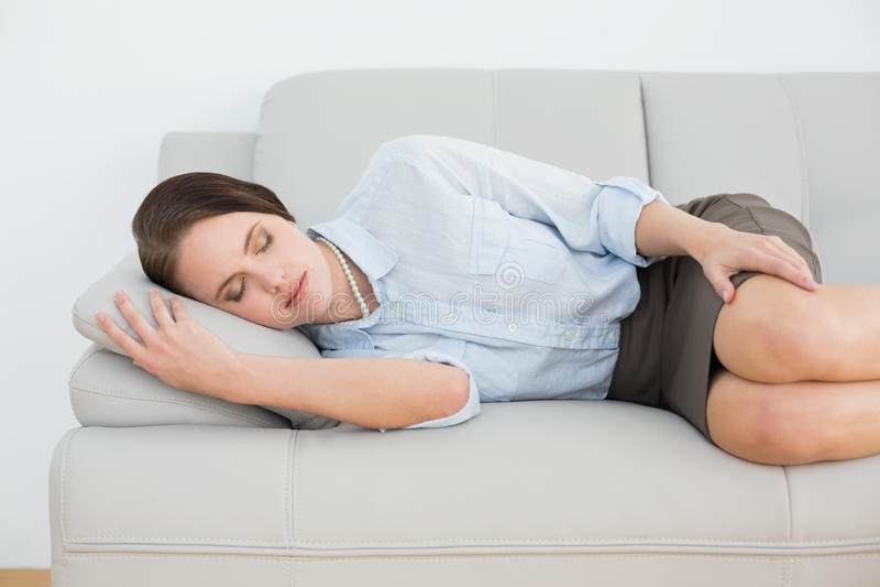 Härlig väl klädd kvinna som sover på soffan arkivbild