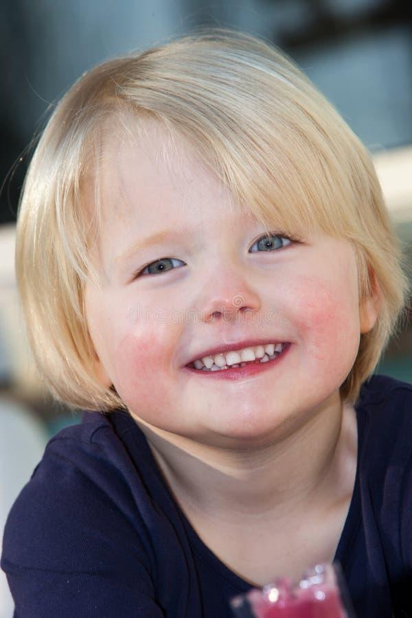 Härlig vänlig blåögd liten blond flicka royaltyfria foton