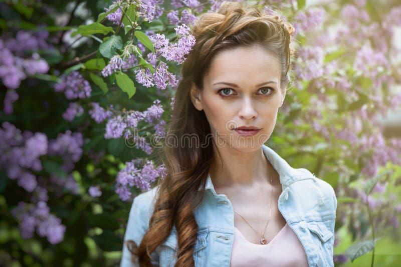 Härlig vårflicka i blommande lila träd arkivfoto