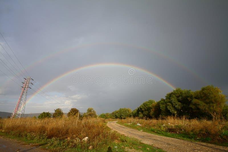 Härlig vårlandskappanorama med ett fält och en regnbåge ovanför den dubbla regnbågesken i himlen, panoramautsikt royaltyfri foto