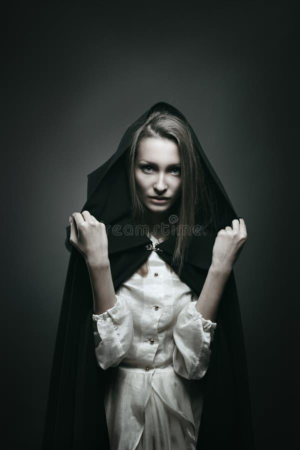 Härlig vampyr med den svarta huven royaltyfri bild