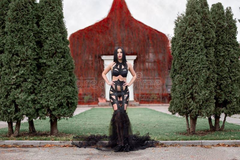 Härlig vampyrkvinna i sexig för klänning blodig slott nära royaltyfri fotografi