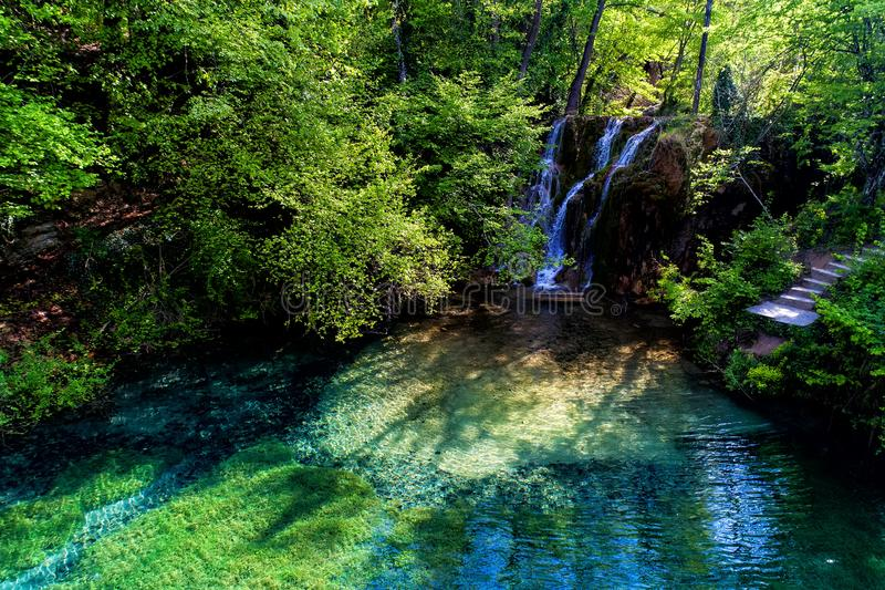 härlig vattenfall och en liten sjö med gräsplanvatten i Skra a royaltyfri fotografi