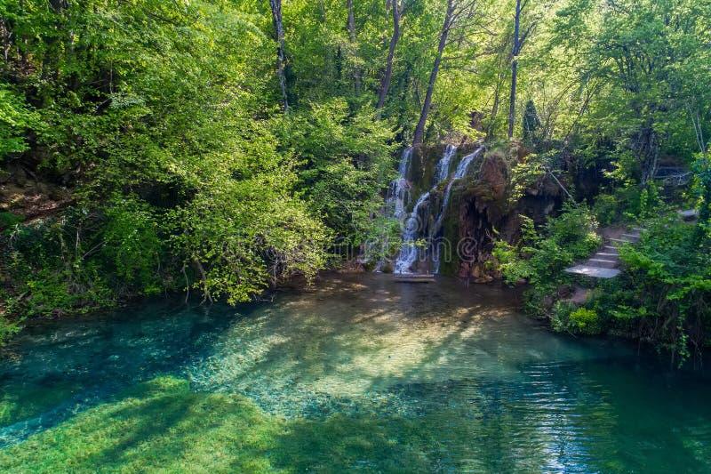 härlig vattenfall och en liten sjö med gräsplanvatten i Skra a arkivfoton