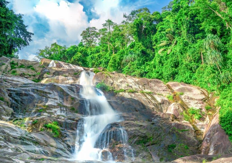 Härlig vattenfall på berget med blå himmel och vita stackmolnmoln Vattenfall i tropisk grön trädskogvattenfall royaltyfri bild