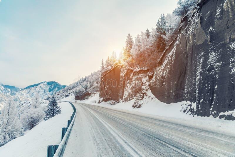 härlig vinter för liggandebergsoluppgång Vintervägen i vaggar Snöig soluppgång i bergen royaltyfri foto