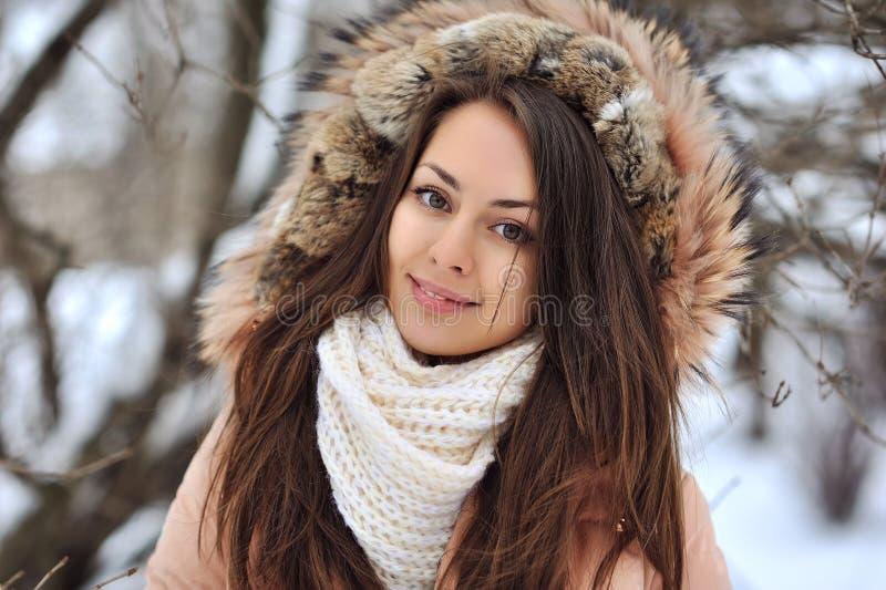 Härlig vinterstående av den unga kvinnan i den snöig scen för vinter arkivfoto