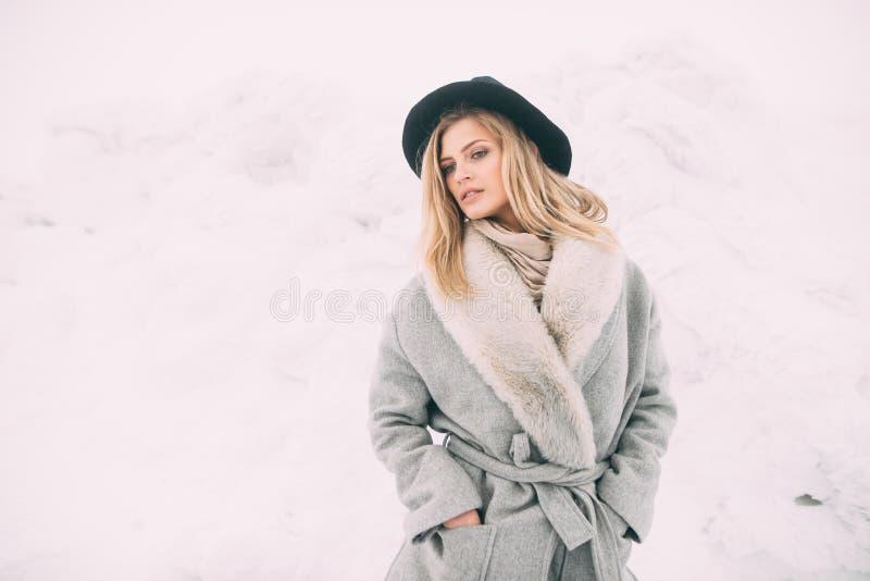 Härlig vinterstående av den unga kvinnan i det snöig landskapet för vinter arkivfoto