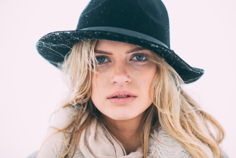 Härlig vinterstående av den unga kvinnan i det snöig landskapet för vinter royaltyfri foto