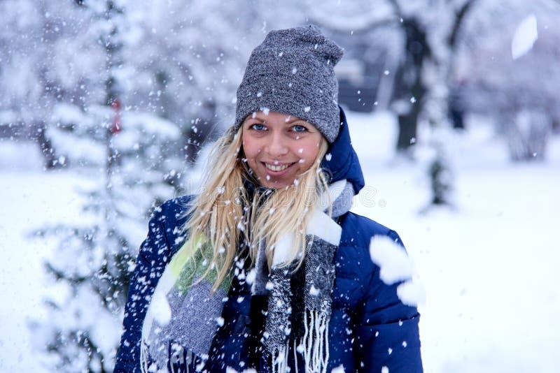 Härlig vinterstående av den unga kvinnan i det snöig landskapet för vinter härlig kläderflickavinter royaltyfri bild