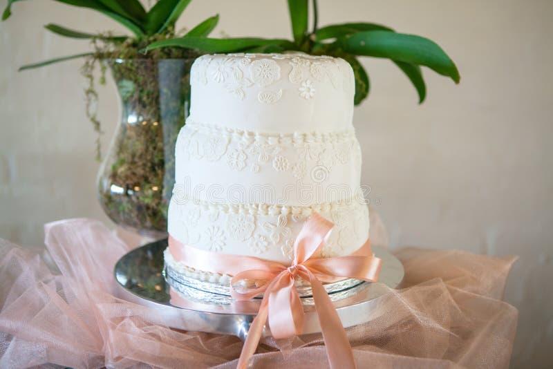 Härlig vit bröllopstårta med garneringdetaljen arkivbilder