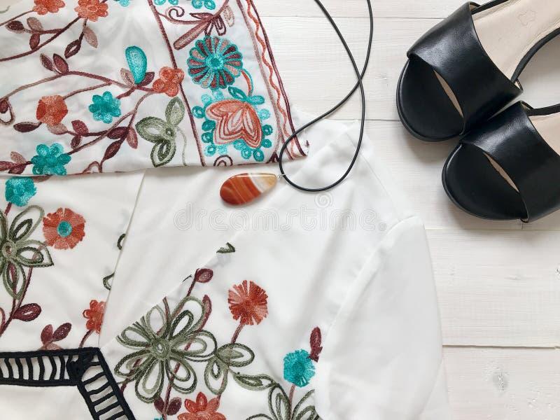 Härlig vit broderad klänning, svarta sandaler och halsband med agat på vit träbakgrund Lekmanna- lägenhet mobilt foto royaltyfri bild