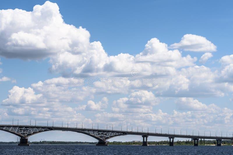 Härlig vit fördunklar ovanför bron till och med floden arkivbilder