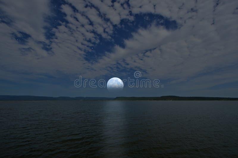 Härlig vit fullmåne och moln i blå himmel över sjön och bergen royaltyfri foto