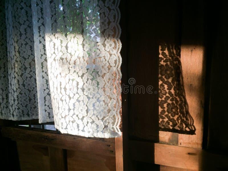 Härlig vit gardin i morgonljus, fönster, skugga och gammal träbakgrund thai hus Varmt tona Bakgrund texturerar arkivbilder