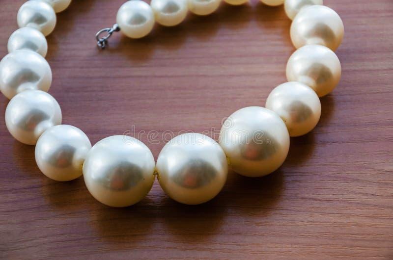 Härlig vit halsband armband som göras av beadson en trätabell arkivbild