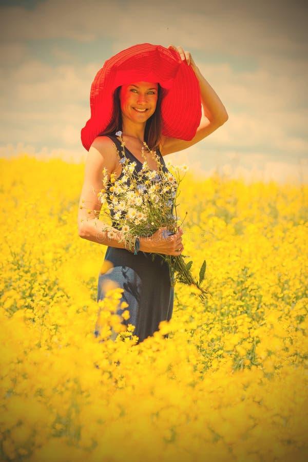 Härlig vit kvinna i en röd hatt och med en bukett av wildfloen royaltyfri fotografi