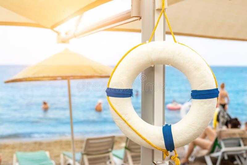 Härlig vit livboj som hängs på paraplyet på den tropiska sandiga stranden Cirkel för livsparare med den härliga blåa havskusten p royaltyfria bilder
