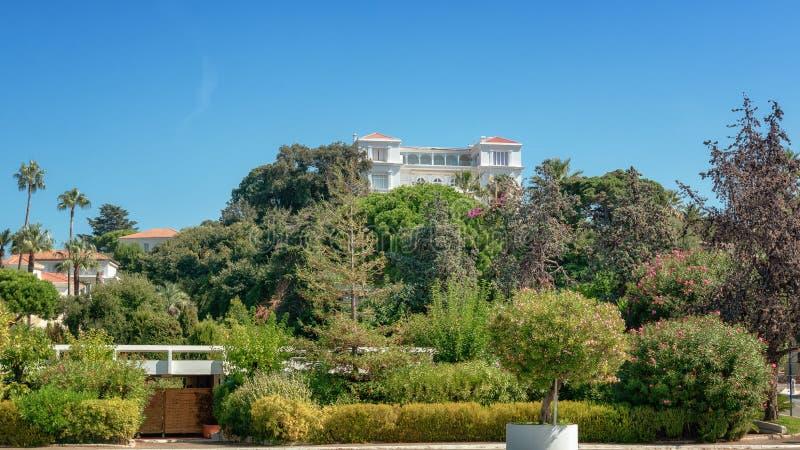 Härlig vit villa på kullen i den franska semesterorten av Juan-les-ben fotografering för bildbyråer