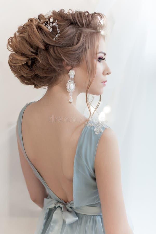 Härlig volymfrisyr för en brud i en försiktig blå ljus klänning med stora örhängen och prydnad i hår arkivbilder