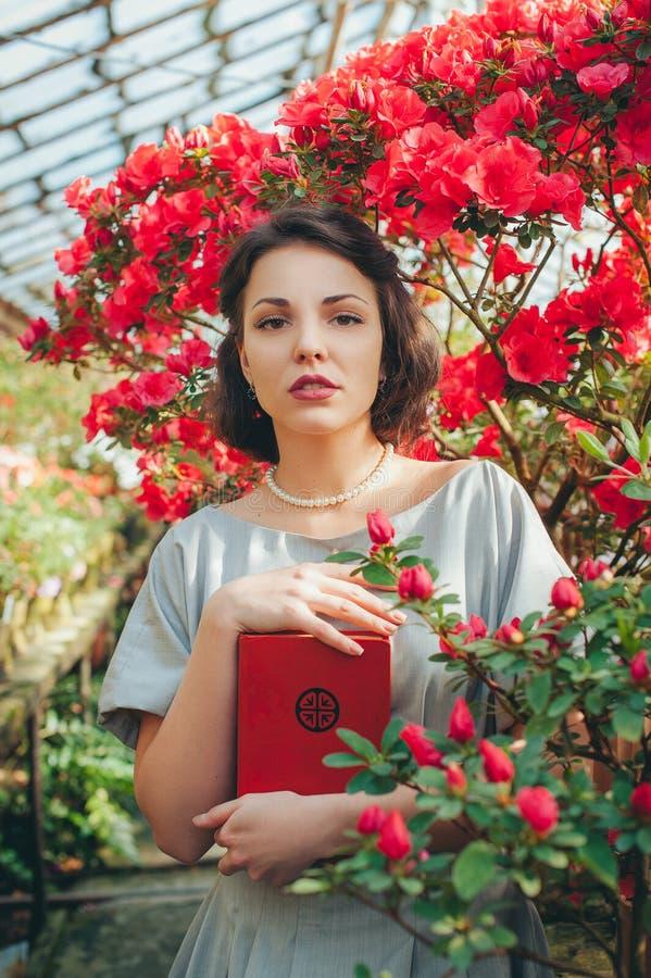 Härlig vuxen flicka i ett azaleaväxthus som läser en bok och drömmer i en härlig retro klänning royaltyfri foto
