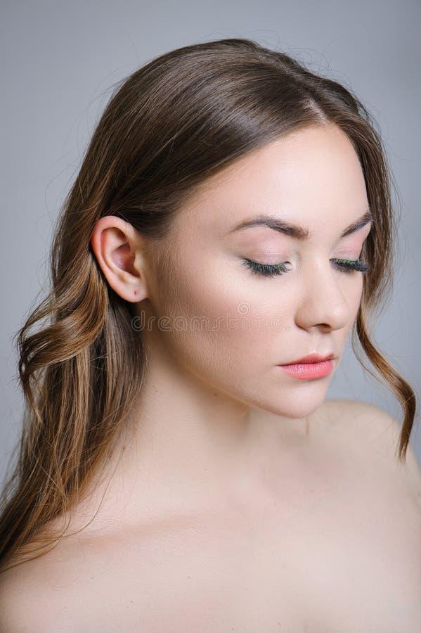Härlig vuxen flicka som poserar med näck makeup med ren hud och att att bry sig hennes hud arkivfoto