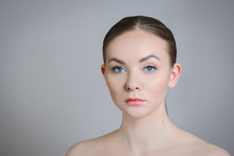 Härlig vuxen flicka som poserar med näck makeup med ren hud och att att bry sig hennes hud royaltyfria foton
