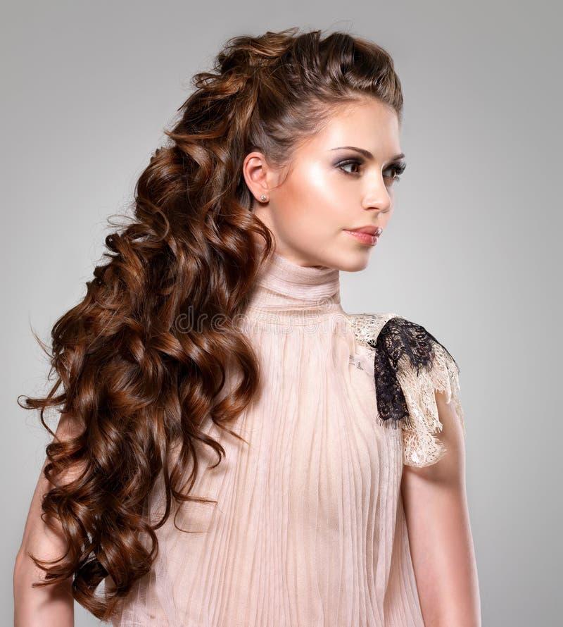Härlig vuxen kvinna med långt brunt lockigt hår. royaltyfri fotografi