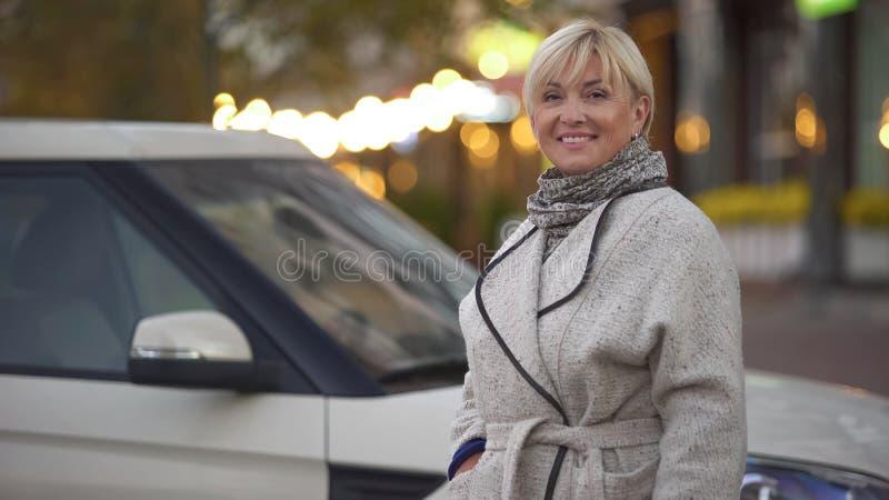 Härlig vuxen kvinna som poserar för kameran nära hennes nya dyra bil, framgång arkivfoton
