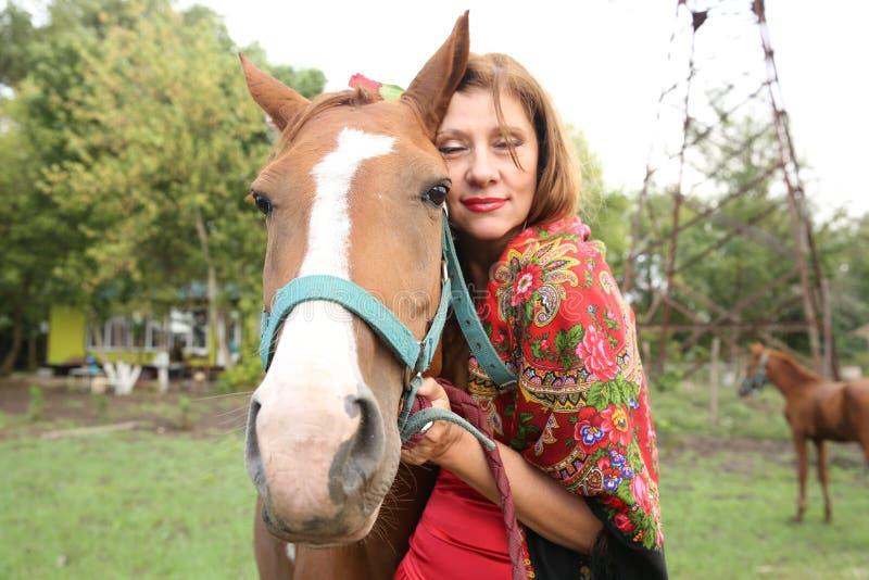 Härlig zigensk flicka i ljus kläder med en häst och hennes föl på en lantgård fotografering för bildbyråer