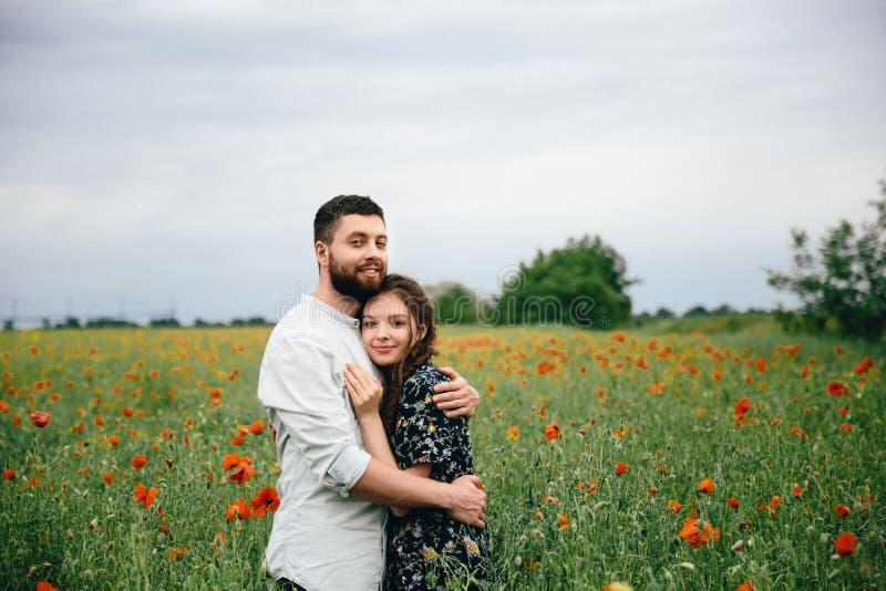 Härliga älska par som vilar på vallmofältbakgrund royaltyfri foto
