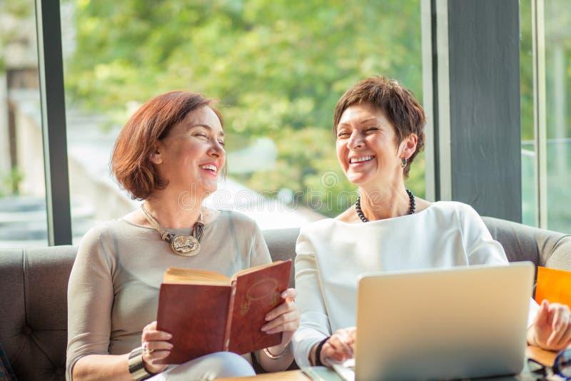 Härliga åldriga kvinnor med att skratta för bärbar dator och för bok royaltyfri fotografi