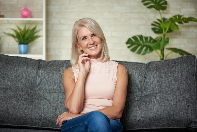 Härliga 50 år kvinna sitter på en soffa hemma royaltyfri fotografi