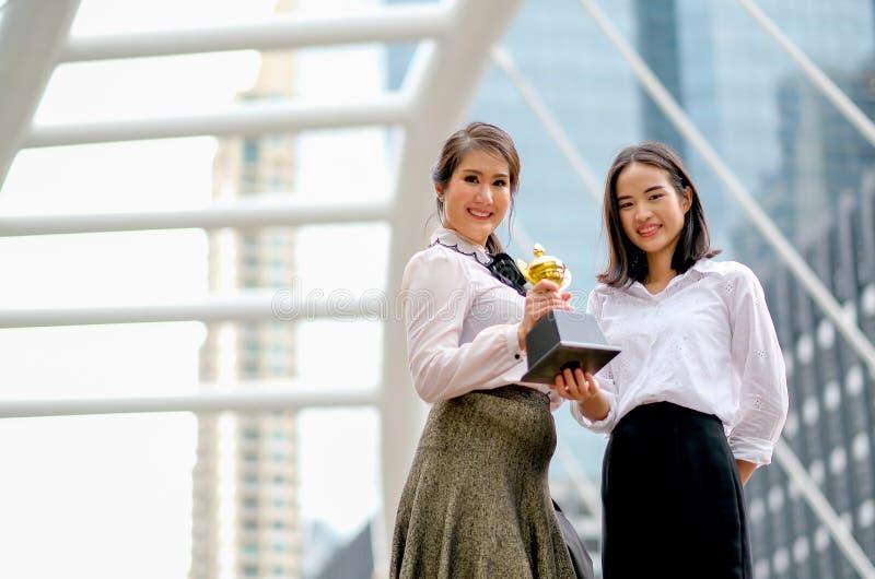 Härliga affärsflickor visar deras trofé av framgången i hennes arbeten och står bland den höga byggnaden i staden arkivbilder