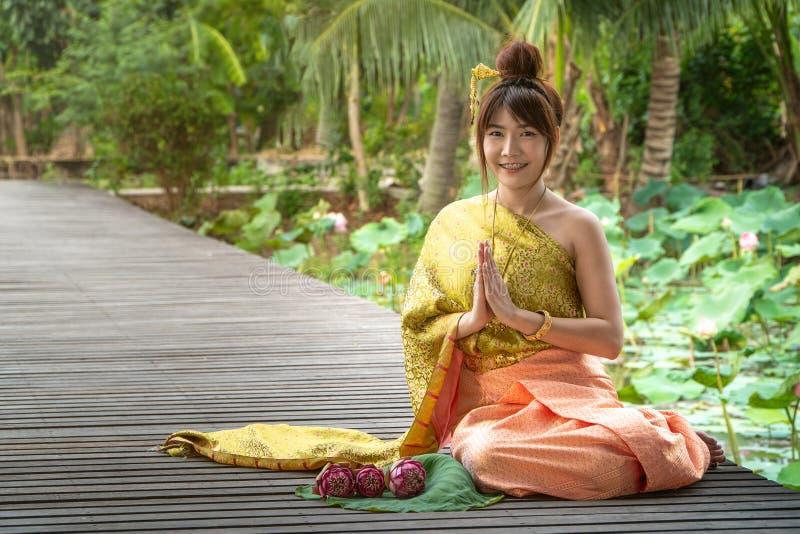 Härliga asia kvinnor som bär den traditionella thailändska klänningen och sitter på träbron Hennes hand är i respekthänderna i de arkivfoto