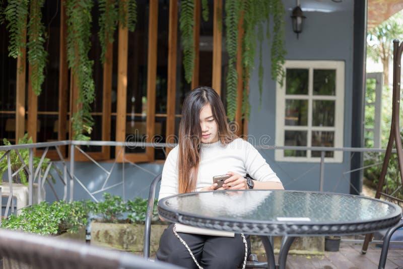 Härliga asiatiska affärskvinnor som placerar i kafé, parkerar brukstelefonen arkivfoton