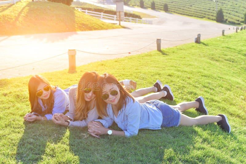 Härliga asiatiska flickor som lägger på det gröna gräset under solljus, w royaltyfri bild