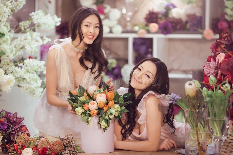Härliga asiatiska kvinnablomsterhandlare med buketten av blommor i blommalager arkivfoto