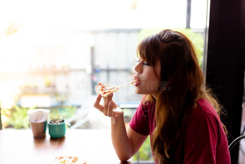 Härliga asiatiska kvinnaförälskelser att äta pizza och tycka om smaken av mozzarellaost så mycket Att charma den härliga kvinnan  arkivbilder