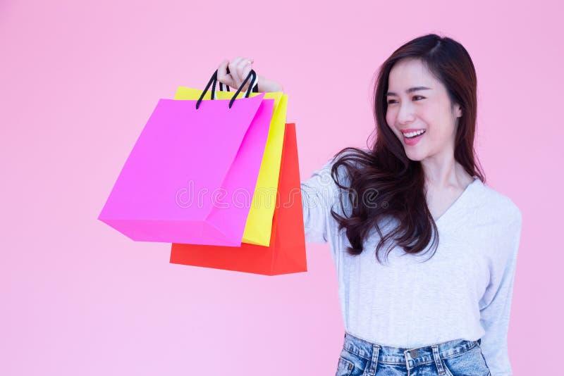 Härliga asiatiska kvinnor shoppar i valentinveckan, tycker om den lyckliga nätta flickan och rymma shoppingpåsar royaltyfri fotografi