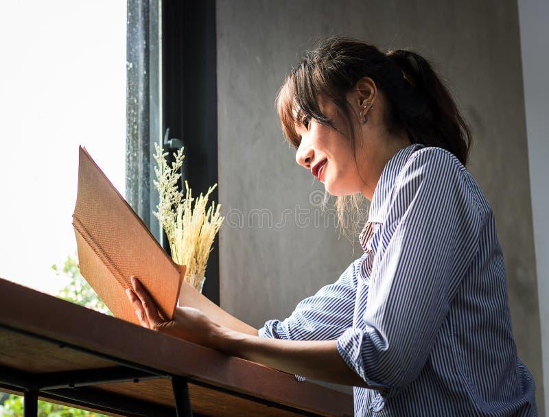 Härliga asiatiska kvinnor som läser stressade böcker arkivbilder