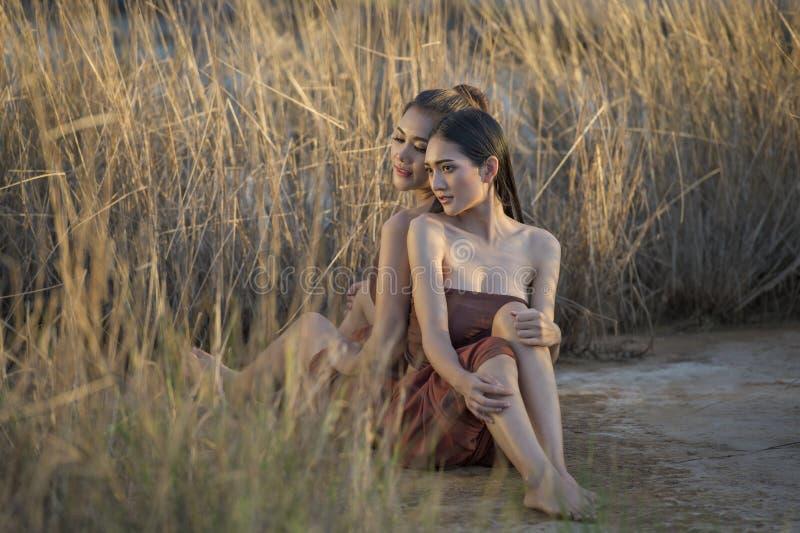 Härliga asiatiska kvinnor som sitter i gräsfältet som bär thailändsk tradition i afton royaltyfri fotografi