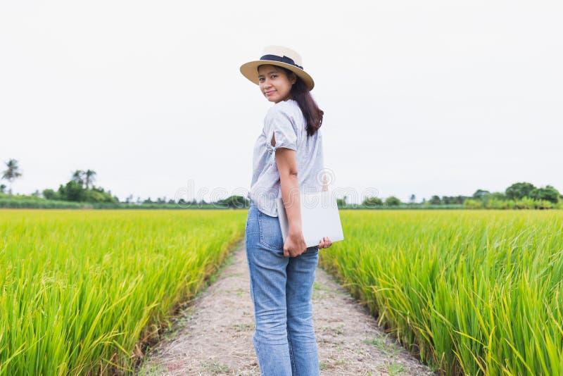 Härliga asiatiska kvinnor som står i risfältet och, rymmer en bärbar datormodell royaltyfria foton