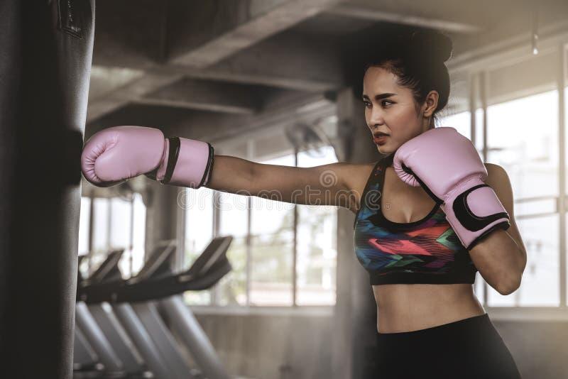 Härliga asiatiska kvinnor stansar sandsäckar i idrottshallen, övningsidéer, viktförlust, muskelbyggnad royaltyfria foton
