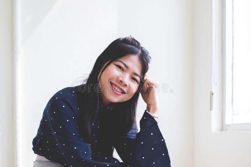 Härliga asiatiska kvinnor, thailändskt folk ser upp Det finns ljust från solen som ner skiner På en vit väggbakgrund arkivfoto