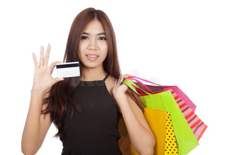 Härliga asiatiska påsar för kvinnahållshopping visar ett craditkort royaltyfri foto