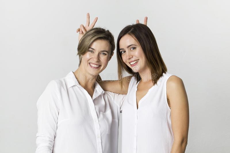 Härliga attraktiva roliga avkopplade bekymmerslösa flickor i den vita skjortan arkivbild