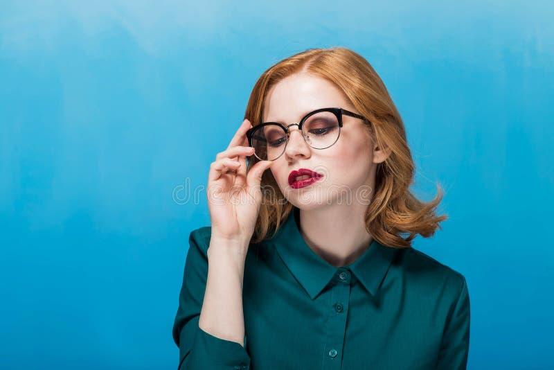 Härliga bärande exponeringsglas för affärskvinna på tabellen som ser kameran på blå bakgrund, royaltyfri fotografi