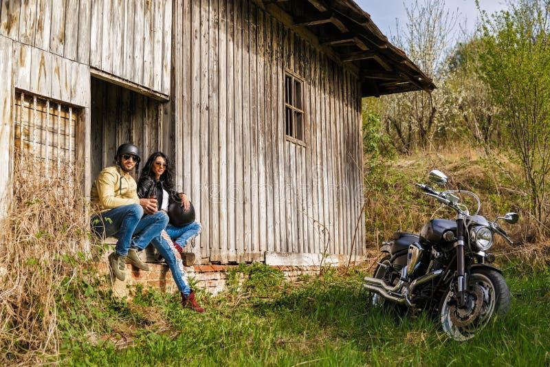 Härliga barnpar med en motorcykel royaltyfria bilder